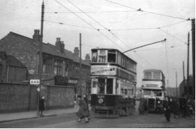 Photo 2 – Tram no 820 outside Cotteridge Tram Depot (to the right) at the terminus of the 36 tram route. This photo was taken on the 24th of February 1952 and the conductor (conductress) is changing the collector pole so that the tram can set off in the opposite direction to the city centre. The shop buildings to the left of the tram are still there on Pershore Road.