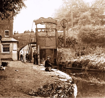 Photo 3 – One of the Guillotine Lock Gates at Lifford Lane Bridge on the Stratford-upon-Avon Canal. The building to the left is the toll collector's office. The lock gates were located about 350 yards from the end of the canal where it joins the Worcester Canal. This first section of the canal was completed to Lapworth by 1802. Since the nationalisation of the canals in 1948, water loss from one canal to another is less of an issue, so the gates are no longer in use and are both left open. The last recorded use of the gates was 1959. This photo shows how fascinated the English are by canals – there are spectators in abundance on the bridge and the canal side even in these early days. Or are they supposed to be working?